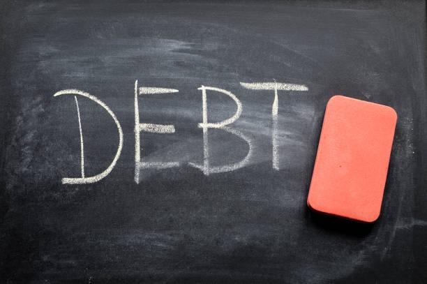 erasing debt, hand written word on blackboard being erased concept